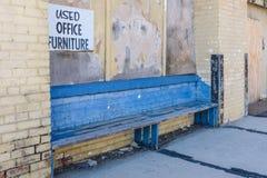 Le vieil extérieur bleu de banc a abandonné l'entrepôt de brique dans le centre urbain photographie stock libre de droits