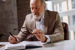 Le vieil homme épuisé met ses verres sur le bureau tout en faisant des notes Photos stock
