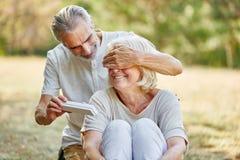 Le vieil homme étonne la femme avec un cadeau Photos stock