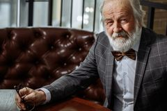 Le vieil homme agréable riche regarde l'appareil-photo photo cultivée par plan rapproché Images libres de droits