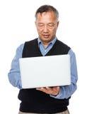 Le vieil homme apprennent à utiliser l'ordinateur portable Photos stock