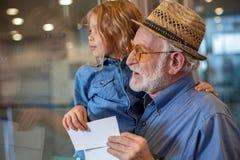 Le vieil homme avec la petite fille attendent l'embarquement Image libre de droits