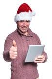 Le vieil homme avec le chapeau de Santa tient un comprimé et fait les sig corrects Photographie stock libre de droits