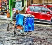 le vieil homme avec le train sur la pluie de rue Image libre de droits