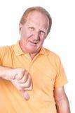 Le vieil homme beau avec le polo orange montre le pouce vers le bas Photographie stock