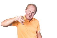 Le vieil homme beau avec le polo orange montre le pouce vers le bas Image libre de droits