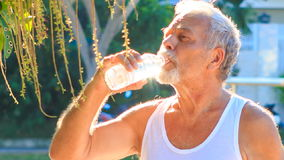 Le vieil homme boit l'eau pendant les exercices de matin en parc banque de vidéos