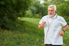 Le vieil homme courant de sourire dans la ville verte se garent images stock