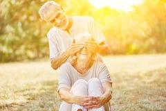 Le vieil homme couvre des yeux du ` s de femme images stock