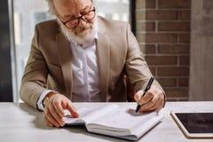 Le vieil homme d'affaires dans la bonne humeur fait le plan d'action Image stock