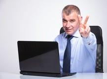 Le vieil homme d'affaires montre la victoire derrière l'ordinateur portable Image libre de droits