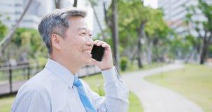 Le vieil homme d'affaires parlent le téléphone Photo stock