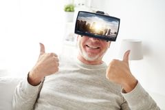 Le vieil homme dans le casque de réalité virtuelle montre des pouces  Images stock