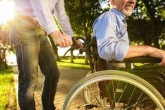 Le vieil homme dans un fauteuil roulant avec son fils en parc Ils ` au sujet de la marche Un homme tient un vieil homme par la ma Photos libres de droits