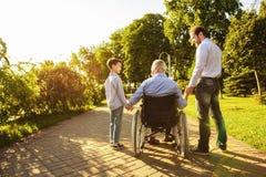 Le vieil homme dans un fauteuil roulant, son fils et petit-fils marchent en parc Image stock