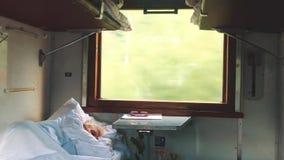 Le vieil homme dort dans le train Intérieur de voyage de chariot de train de voyage de concept vue ferroviaire de chariot d'écono banque de vidéos