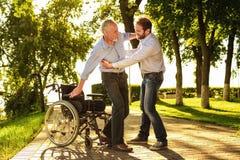 Le vieil homme essaye de sortir du fauteuil roulant sur des béquilles Son fils l'aide Photos libres de droits