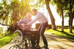 Le vieil homme essaye de sortir du fauteuil roulant sur des béquilles Son fils l'aide Image stock