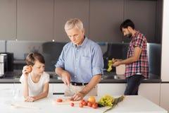 Le vieil homme et le garçon sont occupés à préparer une salade pour le thanksgiving Derrière eux, un homme lave des feuilles de s Photo libre de droits