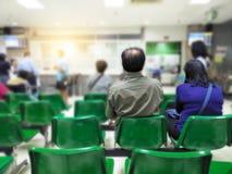 Le vieil homme et la femme adulte s'asseyent sur l'attente verte de chaise médicale et les services de santé à l'hôpital image libre de droits