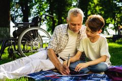 Le vieil homme et son petit-fils s'asseyent sur un pique-nique Ils dessinent avec des crayons dans un carnet Derrière le fauteuil photo libre de droits
