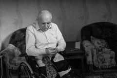 Le vieil homme handicapé essaye de boutonner sa chemise Image libre de droits