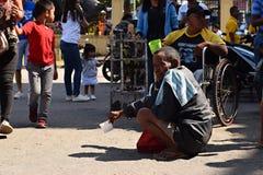 Le vieil homme indigène ethnique prient pour l'aumône à la cour d'église image stock