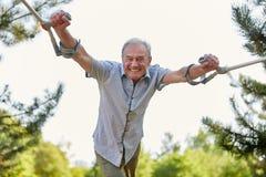 Le vieil homme marche sur des béquilles Photographie stock