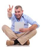 Le vieil homme occasionnel fait des gestes la victoire avec le comprimé Images libres de droits