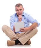 Le vieil homme occasionnel s'assied et regarde d'un air songeur la protection Photo stock