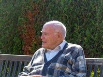 Le vieil homme a plaisir à s'asseoir sur un banc photos stock