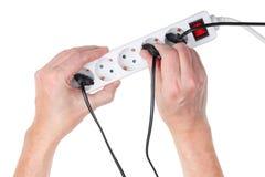 Le vieil homme plus âgé essaye d'insérer un fil avec une prise électrique i Image libre de droits