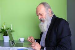 Le vieil homme politique retiré travaille à l'ordinateur dans le bureau pendant la journée Photos libres de droits