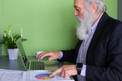 Le vieil homme politique retiré travaille à l'ordinateur dans le bureau pendant la journée Image libre de droits