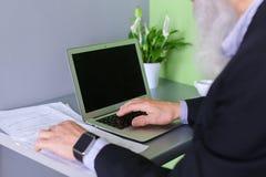 Le vieil homme politique retiré travaille à l'ordinateur dans le bureau pendant la journée Photo libre de droits