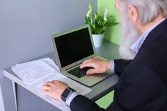 Le vieil homme politique retiré travaille à l'ordinateur dans le bureau pendant la journée Photos stock