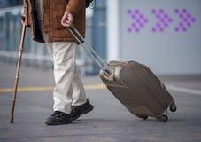 Le vieil homme porte sa valise tout en se reposant sur la canne Image stock