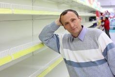 Le vieil homme se penche contre les étagères vides Image libre de droits