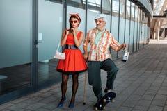 Le vieil homme se promène d'un pas nonchalant avec une jeune fille photo libre de droits
