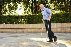 Le vieil homme sur des béquilles flâne par le parc Il est focalisé Photographie stock libre de droits
