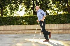 Le vieil homme sur des béquilles flâne par le parc Il est focalisé Photo stock
