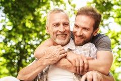 Le vieil homme sur un fauteuil roulant et son fils marchent en parc Un homme étreint son père plus âgé Photos stock