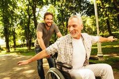 Le vieil homme sur un fauteuil roulant marche en parc avec son fils adulte Ils dupent autour Images stock