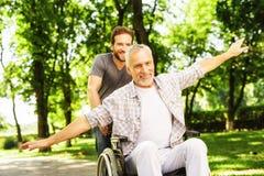 Le vieil homme sur un fauteuil roulant marche en parc avec son fils adulte Ils dupent autour Photo stock