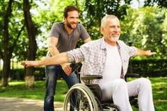Le vieil homme sur un fauteuil roulant marche en parc avec son fils adulte Ils dupent autour Image stock