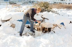 Le vieil homme turc non identifié met les bois coupés du feu dans un seau en plastique Image libre de droits