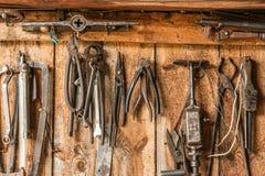 Le vieil outil de travail sur le fond des panneaux en bois, les outils de l'artisan accrochent sur des clous Image libre de droits