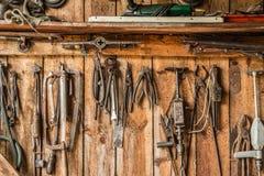 Le vieil outil de travail sur le fond des panneaux en bois, les outils de l'artisan accrochent sur des clous Images libres de droits