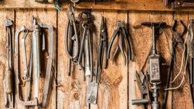 Le vieil outil de travail sur le fond des panneaux en bois, les outils de l'artisan accrochent sur des clous Images stock