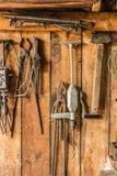 Le vieil outil de travail sur le fond des panneaux en bois, les outils de l'artisan accrochent sur des clous Image stock